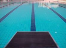 Bloques el comenzar en la fila por la piscina, foco selectivo Plataforma del salto para nadar en piscina y backgroun de la grader fotos de archivo