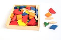 Bloques multicolores de madera en una caja de madera en un fondo blanco Fotografía de archivo libre de regalías