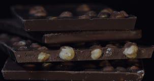 Bloques oscuros del chocolate con la inclinación macra del primer lento de los detalles de las nueces Perspectiva hecha de barras almacen de video