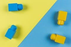 Bloques plásticos azules y amarillos de la construcción en fondo amarillo y azul Fotos de archivo libres de regalías