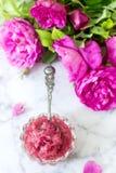 Bloquez avec des pétales de rose dans un bol en verre et des roses lumineuses sur un fond clair Photographie stock