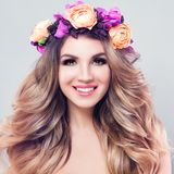 Blossom Beauty. Beautiful Woman Spa Model. Cheerful Woman Spa Model with Healthy Skin, Cute Smile, White Teeth, Blonde Curly Hairstyle, Makeup and Summer Flowers Stock Photos