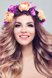 Blossom Beauty. Beautiful Woman Spa Model. With Wavy Blonde Hair, Makeup and Colorful Flowers Wreath, Perfect Female Face Closeup Stock Photography