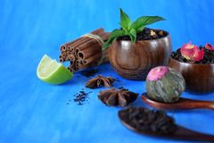 Blossom, black and green sorts of tea in wooden cups and spoons. And two anise stars against the blue background stock photo