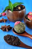 Blossom, black and green sorts of tea in wooden cups and spoons. And two anise stars against the blue background royalty free stock photo