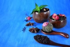 Blossom, black and green sorts of tea in wooden cups and spoons. And two anise stars against the blue background stock image