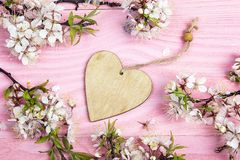 Blossoming apple tree branches with decorative heart on pink woo Royalty Free Stock Photo
