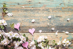 Blossoming apple tree branches with decorative hearts on wooden Stock Photo