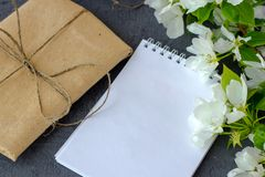 Floral composition. Pretty gift box wrapped with brown craft paper royalty free stock photos