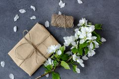Floral composition. Pretty gift box wrapped with brown craft paper royalty free stock image