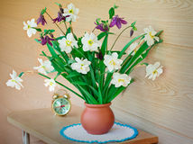 Blossoming narcissuses in a vase on a table. Royalty Free Stock Photo