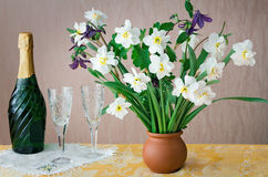 Blossoming narcissuses in a vase on a table. Stock Image