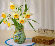 Blossoming narcissuses in a vase on a table. Stock Images