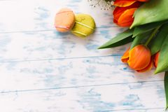 Blossoming tulips with macaroons on a light wooden background. Still life, spring concept Stock Photo