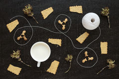 Blossoming twigs, milk, cotton skein and cookies Stock Photo