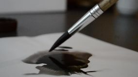 Blot from the ink left by a brush on white paper. Blot from the ink left by a brush on white paper stock footage