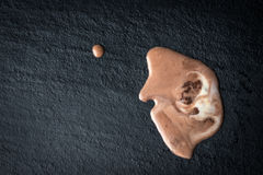 Blotted melted ice cream. On dark food background stock photos
