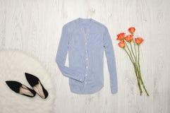 Blouse in fine strepen, schoenen en oranje rozen op een houten achtergrond modieus concept Stock Afbeeldingen