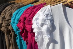 Blouses. Of different colors hanging on hangers royalty free stock image
