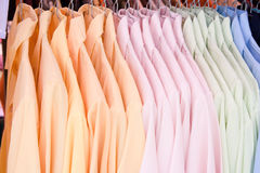 Blouses. Several coloured blouses hanged in the shop Stock Photos