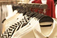 Blouses op een hanger in boutique van de kleren van vrouwen stock afbeelding