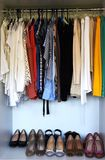 Clothes and shoes in the wardrobe royalty free stock image