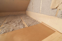 Blow-in cellulose fiber wool insulation. Photo of a cellulose wool insulation that has been blown to the walls and floor stock image