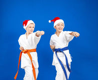 Blow hand the boys are beating in caps of Santa Claus Royalty Free Stock Photography