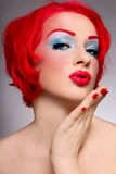 Blow kiss. Portrait of young beautiful redhead girl with fancy make-up throwing kiss Stock Image