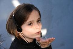 Blow a kiss. Cute teenage girl with earphones  blows a kiss Stock Photography