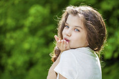 Blow kiss, young caucasian female haired model. On the background of summer park Royalty Free Stock Photo