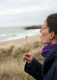 Blowball. Profile of girl with blowball on beach , background is out of focus royalty free stock photography