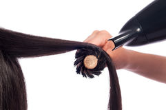 Blowdry Straight Hair. Isolated photo of a coiffeur client getting blowdry her hair. She is a brunette getting her straight hair done. The blowdryer and brush is royalty free stock image