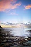 Blowhole on rocky coastline Stock Images