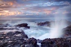 Blowhole on rocky coastline Stock Photo