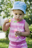 Blowing. Little girl blowing soap bubbles Stock Images