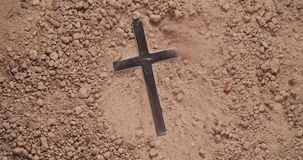 Blowing away dirt to discover hidden metal cross
