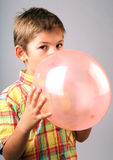 Blowing balloon. Child blowing red balloon stock images