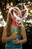Blowing big bubbles. Little girl blowing huge bubbles in the garden Stock Photos