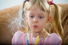 Blowing on a birthday candle. The girl in the hands of a cake with six candles - it's birthday and she blows out the candles to make a wish Royalty Free Stock Photography