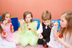 Blowing bubbles. Group of preschool kids blowing bubbles at the birthday party Royalty Free Stock Photo