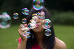 Blowing Bubbles. Mid twenties brunette woman blows bubbles in the park royalty free stock image