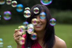 Blowing Bubbles. Mid twenties brunette woman blows bubbles in the park royalty free stock photos