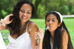 Blowing bubbles. Mom and daughter blowing bubbles in the park stock image