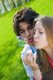 Blowing bubbles. Attractive multi-racial couple in love blowing bubbles on nature Royalty Free Stock Photography