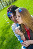 Blowing bubbles. Attractive multi-racial couple in love blowing bubbles on nature Stock Image