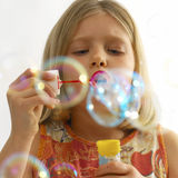 Blowing bubbles. Young girl concentrating on blowing bubbles Royalty Free Stock Photos
