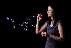 Blowing bubbles. Attractive young brunette blowing bubbles, isolated on black Stock Photos