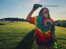 Blowing bubbles. Boy wearing tie dye shirt making bubbles Stock Image