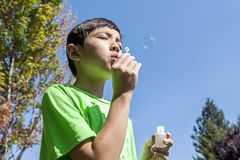 Blowing bubbles on a bright day. Stock Photo